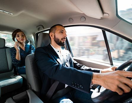 Rideshare driver driving a car with businesswoman in backseat. Woman talking on mobile phone.